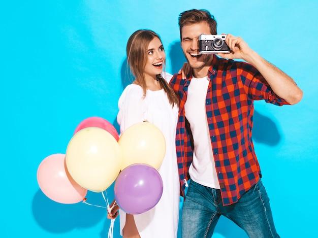 Lächelndes schönes mädchen und ihr hübscher freund, die bündel bunte ballone hält. glückliches paar, das foto von selbst auf retro- kamera macht. alles gute zum geburtstag