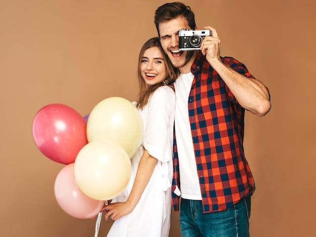 Lächelndes schönes mädchen und ihr hübscher freund, die bündel bunte ballone hält. glückliches paar, das foto von selbst macht. alles gute zum geburtstag