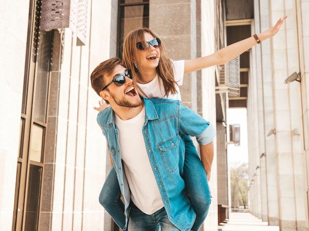 Lächelndes schönes mädchen und ihr hübscher freund in der zufälligen sommerkleidung. mann mit seiner freundin auf dem rücken und sie hob die hände.