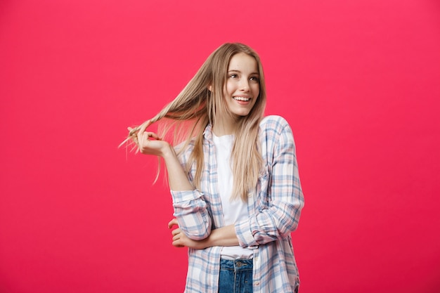 Lächelndes schönheitsporträt mit den gekreuzten armen auf rosa hintergrund