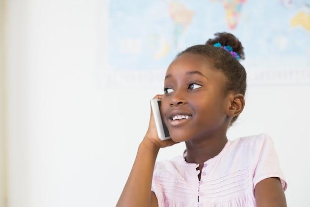 Lächelndes schulmädchen, das am handy im klassenzimmer spricht