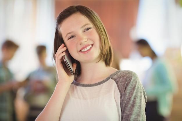 Lächelndes schulmädchen, das auf handy im korridor spricht