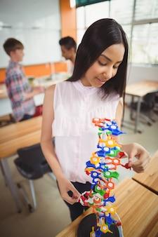 Lächelndes schulmädchen, das das molekülmodell im labor untersucht