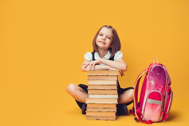 Lächelndes schulmädchen, das hinter einem stapel büchern mit rucksackkonzept des lernens und der schule sitzt