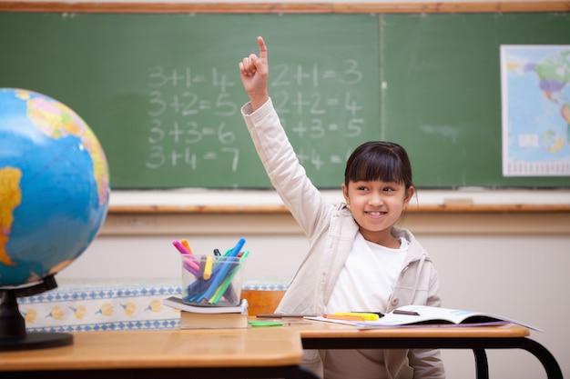 Lächelndes schulmädchen, das ihre hand anhebt, um eine frage zu beantworten
