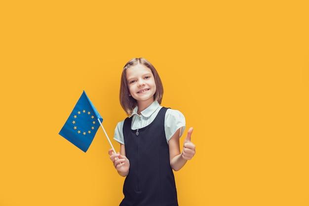 Lächelndes schulmädchen mit der flagge der europäischen union, das daumenbildung im europäischen konzept zeigt