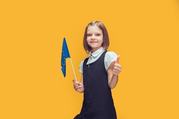Lächelndes schulmädchen mit kleiner flagge der europäischen union, die daumenbildung im europäischen konzept zeigt