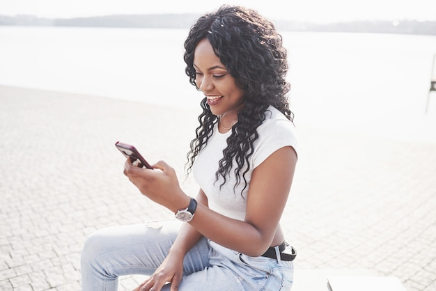 Lächelndes schwarzes mädchen mit einem telefon am wasser