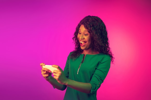 Lächelndes, scrollendes telefon. afroamerikanische junge frau auf rosa hintergrund mit farbverlauf im neonlicht. schönes weibliches modell. konzept der menschlichen emotionen, gesichtsausdruck, verkauf, anzeige. flyer mit exemplar.