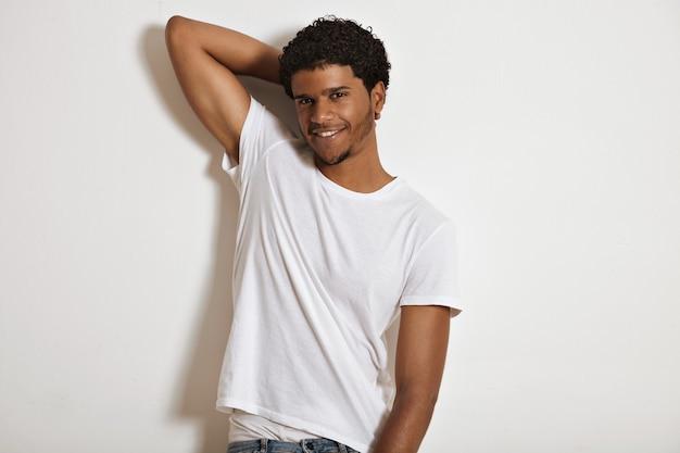 Lächelndes sexy afroamerikanisches modell, das ein weißes leeres baumwoll-t-shirt trägt, das seine hand hebt und seine weiße unterwäscheshow von jeans macht