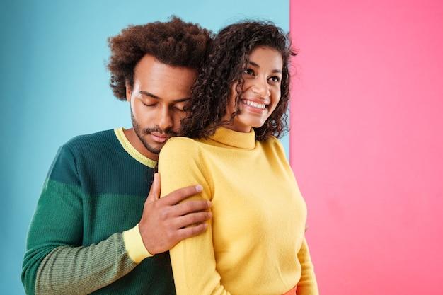 Lächelndes sinnliches afrikanisches paar, das über buntem hintergrund umarmt