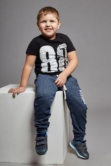 Lächelndes sitzen des jungenkindes auf einem weißen würfel