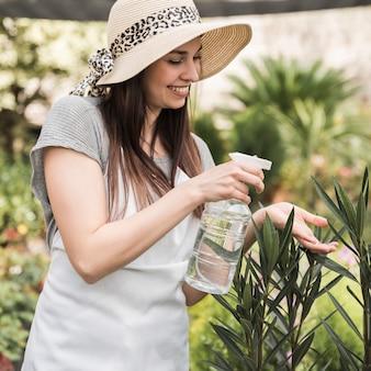Lächelndes sprühwasser der tragenden hut der jungen frau auf grünpflanze