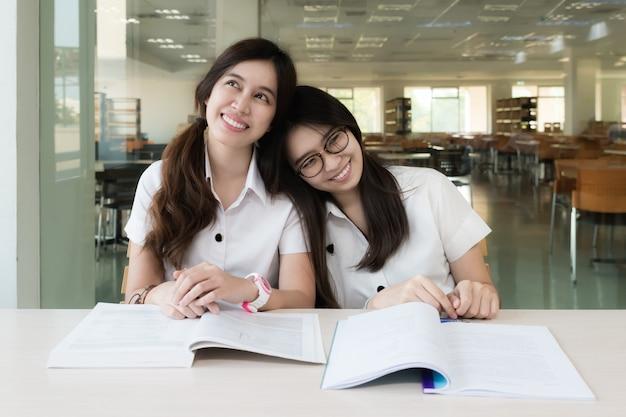 Lächelndes studentenmädchen des asiaten zwei in der bibliothek studierend und tagesträumen.