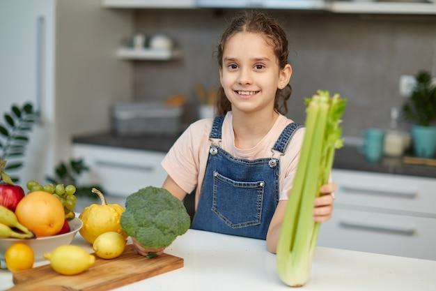 Lächelndes süßes kleines mädchen steht in der nähe des tisches in der küche und hält grünen brokkoli und sellerie in den händen.