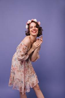 Lächelndes süßes mädchen mit rosen im stehenden haar. entzückende europäische dame im sommerkleidertanzen.