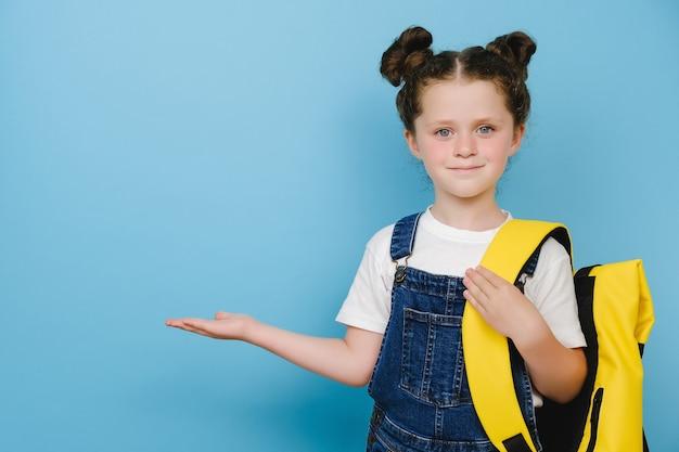 Lächelndes süßes schulmädchen-kind zeigt kopienraum für werbeinhalte, trägt gelben rucksack und t-shirt und steht einzeln auf blauem hintergrund im studio. bildung, schulkonzept