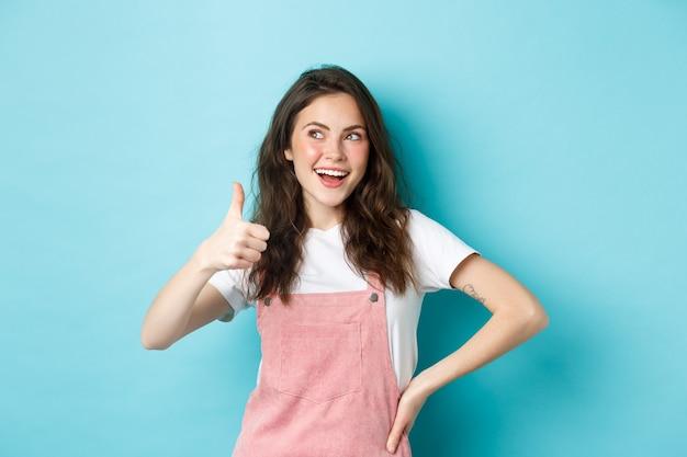 Lächelndes süßes teenie-mädchen mit schönem rouge und glamour-make-up, daumen nach oben zur zustimmung zeigend, blick auf das banner in der oberen linken ecke, empfehlung des ladens, stehend vor blauem hintergrund.
