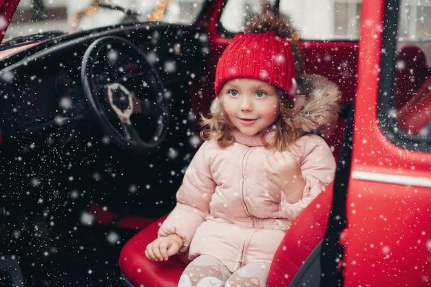 Lächelndes süßes wintermädchen mit rotem hut, das im auto sitzt und spaß mit mittlerem schuss hat. glückliches schönes weibliches baby in warmer kleidung mit positiven emotionen im freien, umgeben von schneeflocken, die die kindheit genießen