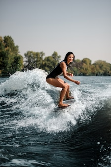 Lächelndes surfgirl auf einem surfbrett nahe küste