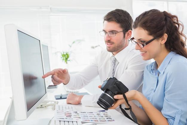 Lächelndes team, das mit computer und digitalkamera arbeitet