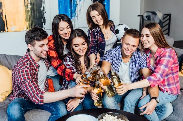 Lächelndes team von arbeitskräften nach job entspannte sich zu hause mit bier.