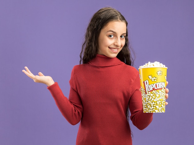 Lächelndes teenager-mädchen, das einen eimer popcorn hält und nach vorne schaut und die leere hand zeigt, die auf lila wand isoliert ist?