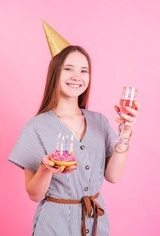 Lächelndes teenagergeburtstagsmädchen im geburtstagshut, der zwei donuts mit kerzen lokalisiert auf rosa hält