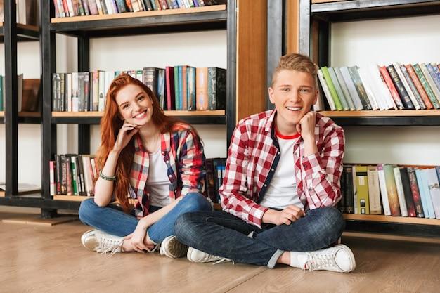 Lächelndes teenagerpaar, das auf einem boden am bücherregal sitzt