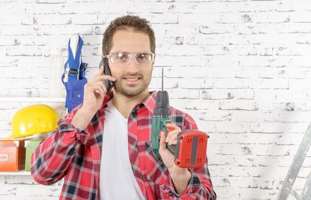 Lächelndes telefon des jungen arbeitnehmers in seinem studio