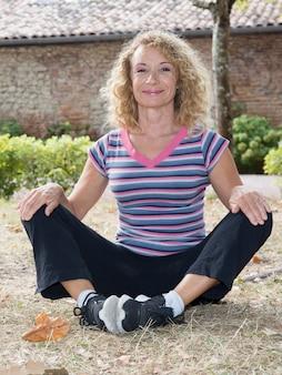 Lächelndes übendes yoga der reifen frau im park