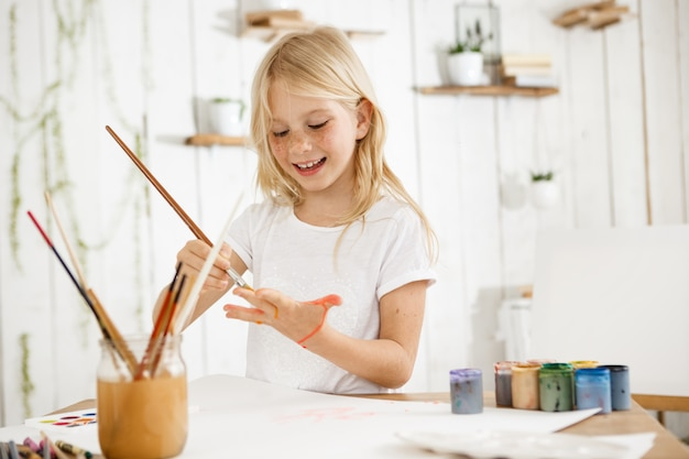 Lächelndes und glückliches kleines blondes mädchen im weißen t-shirt, das etwas auf ihrer handfläche mit einem pinsel zeichnet
