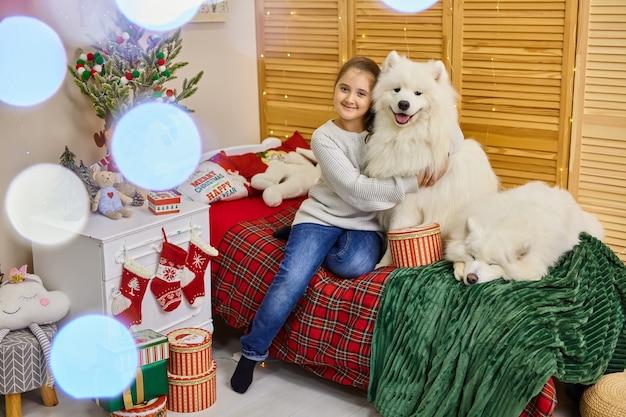 Lächelndes verspieltes süßes kleines mädchen, das große weiße flauschige samojeden umarmt