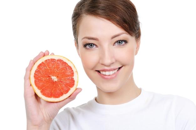 Lächelndes weibliches gesicht mit frischer grapefruit in ihren händen