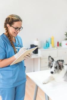 Lächelndes weibliches tierarztschreiben auf klemmbrett mit hund auf tabelle in der klinik