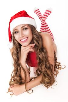 Lächelndes weihnachtsmädchen im roten bodysuit und gestreiften strümpfen sitzt