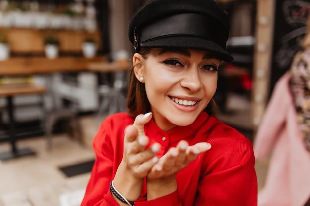 Lächelndes, zartes pariser mädchen im stilvollen outfit sendet luftkuss. porträt der jungen frau mit ausdrucksstarkem blick