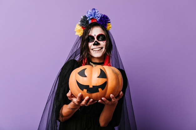Lächelndes zombiemädchen im schwarzen schleier, der auf pastellwand aufwirft. frohe frau im toten brautoutfit, das halloween-kürbis hält.
