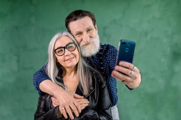 Lächelndes zufriedenes älteres paar, das zusammen auf telefonkamera für selfie-foto schaut