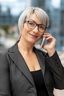 Lächelnfrau, die am telefon spricht und kamera betrachtet