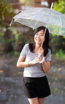 Lächelnfrau im regen mit regenschirm