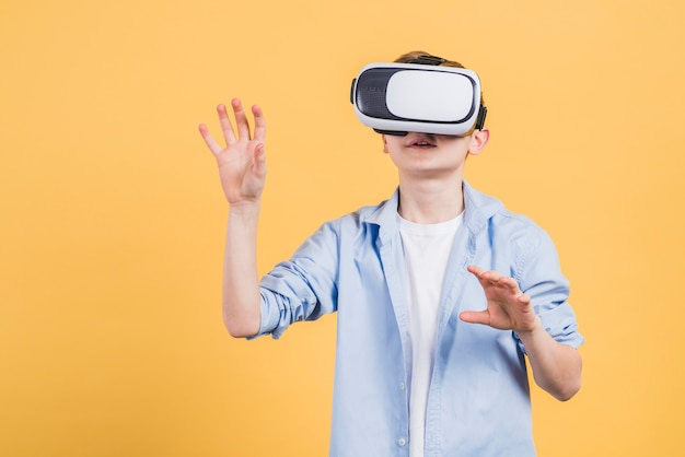 Lächelnjunge, der den gläserkopfhörer der virtuellen realität trägt, der seine hände in einer luft gegen gelben hintergrund bewegt