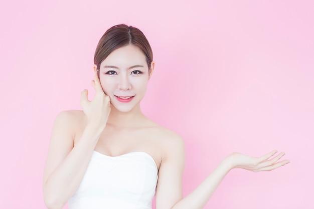 Lächelnmädchen, das den leeren kopienraum darstellt ihr produkt auf rosa zeigt