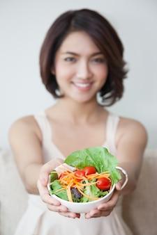 Lächelnschönheiten mit schüssel salat