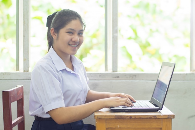 Lächelnstudentin, die computer oder laptop im klassenzimmer spielt.