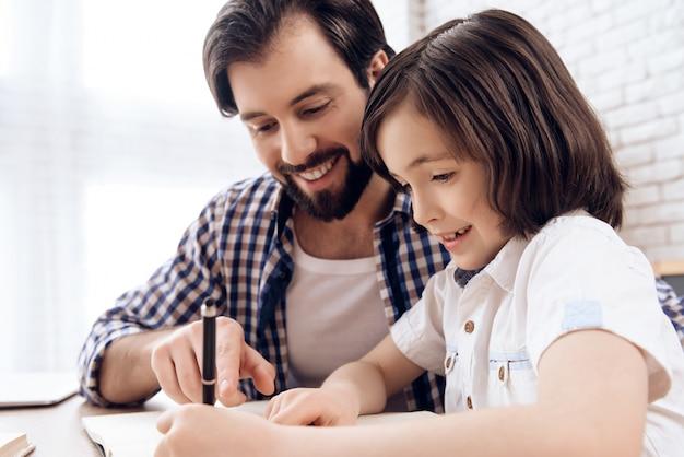 Lächelnvater hilft jungem sohn, schulhausaufgaben zu erledigen.