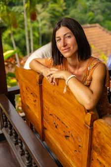 Lächle weiter. fröhliche weibliche person, die auf dem sofa sitzt, während sie sich in einem exotischen land ausruht
