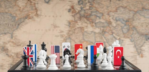 Länderflaggensymbole auf dem schachbrett mit figuren auf dem hintergrund der politischen karte