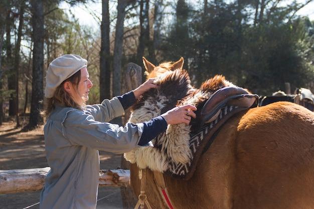 Ländliche frau sattelt ihr pferd auf dem feld