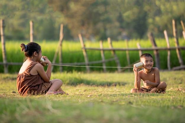Ländliche kinder kommunizieren mit dem telefon.